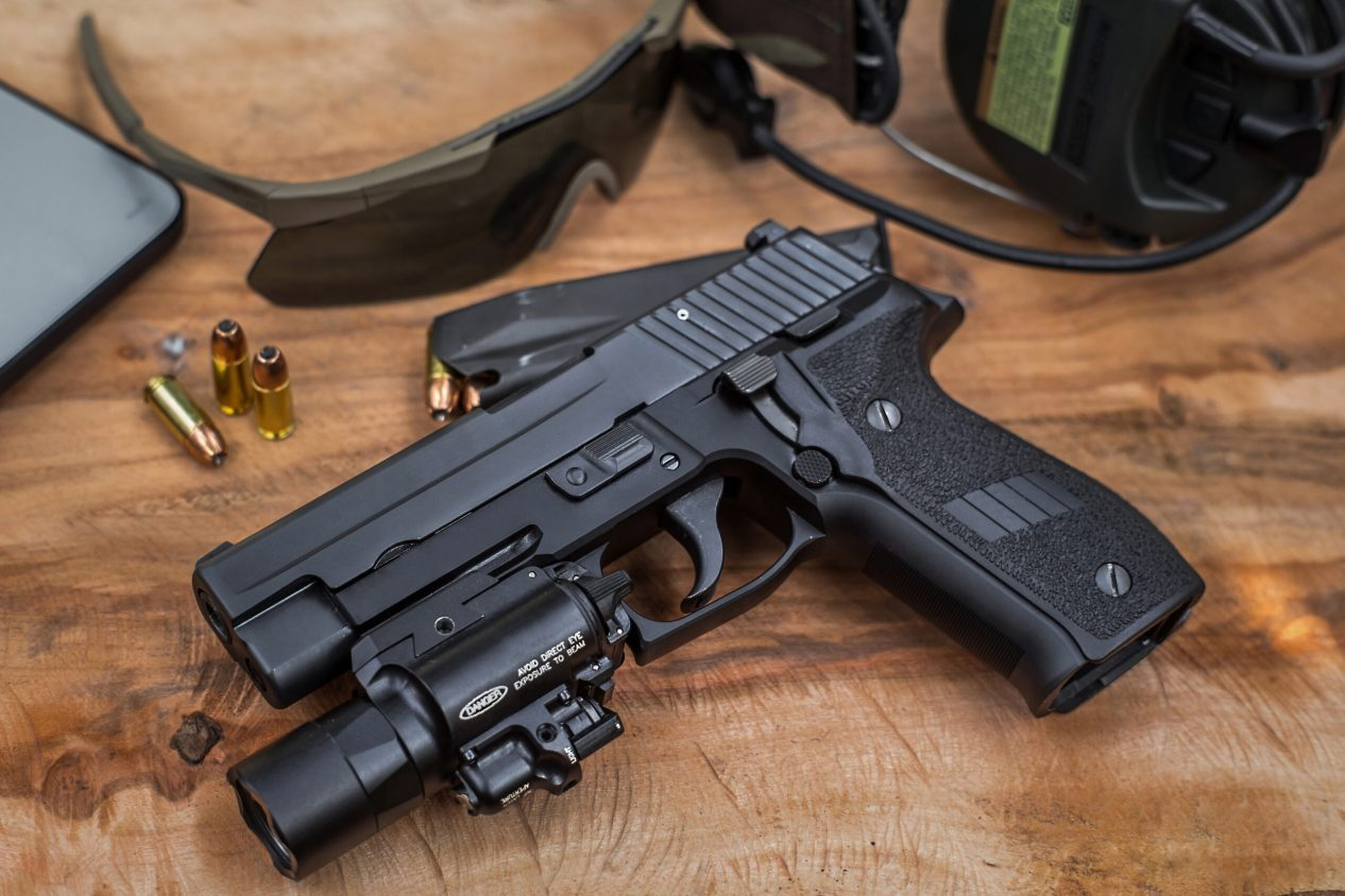 SIG P226 with light on table with sunglasses, magazine and ammo