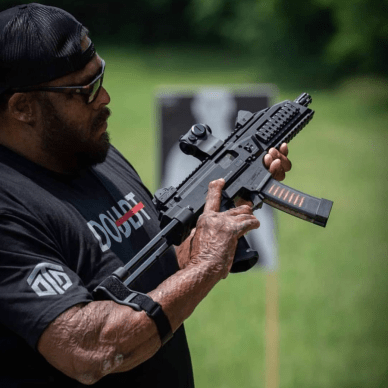 """Omar """" Crispy 11B"""" Avila holding an AR-15 pistol with a stabilizing brace attached to his arm."""