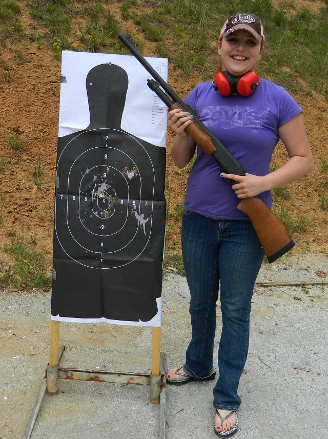 young lady holding a pump-action shotgun next to paper target with a dirt berm in the background