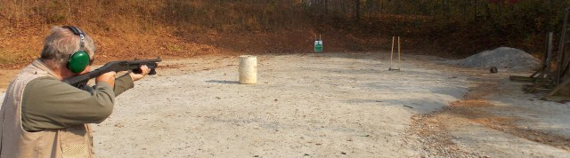 Shooting a pump-action shotgun loaded with slugs at a paper target 50 yards away