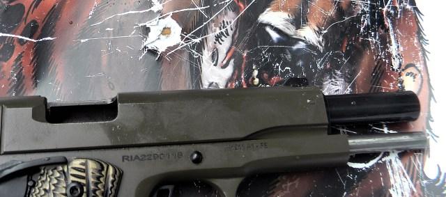 rock island fs 1911 pistol with slide locked back back on a wild boar paper target