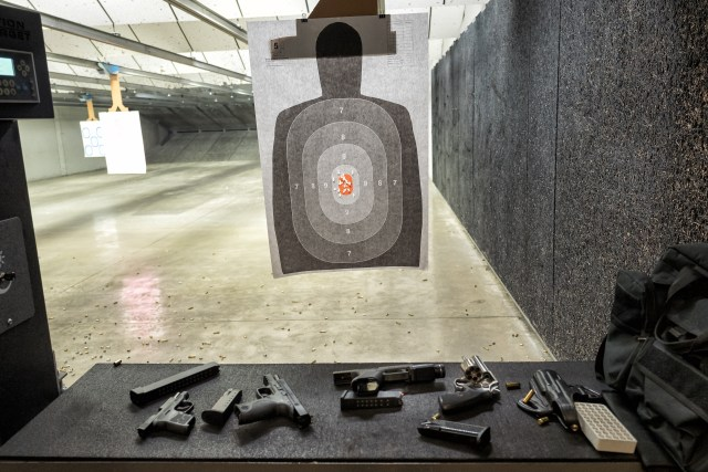 gun range booth with target and handguns.