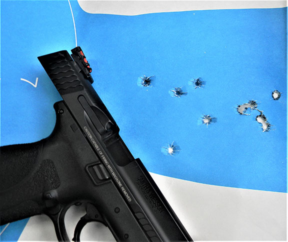 Smith & Wesson Military & Police Pro Series pistol with the slide locked to the rear resting on a paper silhouette target