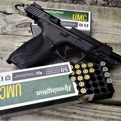 Smith & Wesson Military & Police Pro Series 5.0 pistol with slide locked to the rear resting between two boxes of Remington UMC ammunition