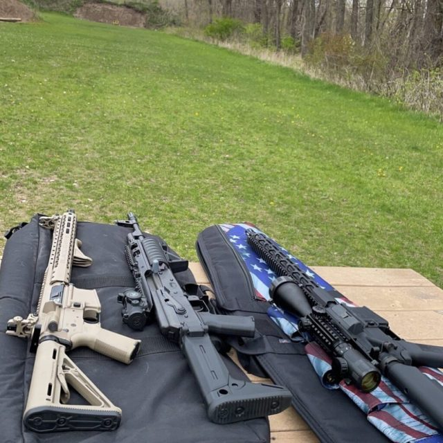 Two AR-15s and one AK on table at range