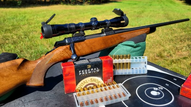 bolt action rifle with scope on shooting bench