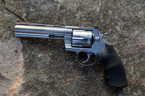 Colt Anaconda Revolver .44 magnum left profile stainless-steel with a rock background