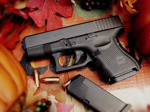 Glock 26 pistol on autumn leaves