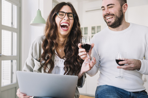 laughing-couple-with-wine-notebook_23-2147766982