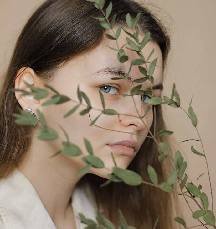 Girl with blue eyes and plant over her face