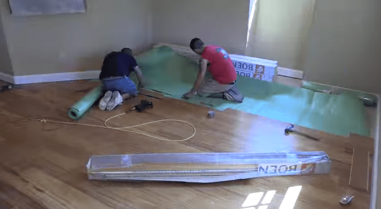 Rolling out a flooring underlayment