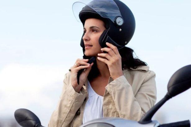 Mujer colocándose casco de moto- Claro Shop