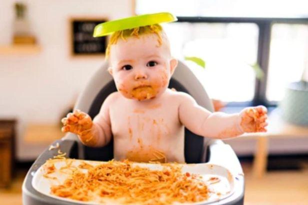 Bebé en silla alta comiendo pasta