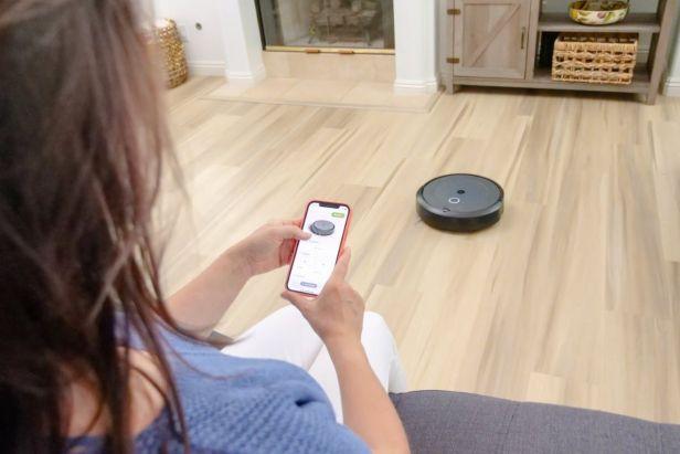 mujer controlando aspiradoroa robot con aplicación - Claro Shop