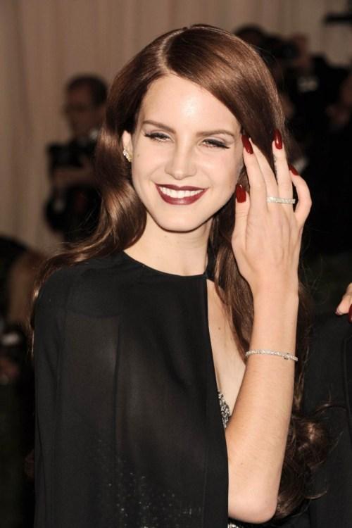 Lana del Rey al Galà del Met: con quel mantello e le unghie lunghe dello stesso colore del rossetto è una perfetta ispirazione per Halloween