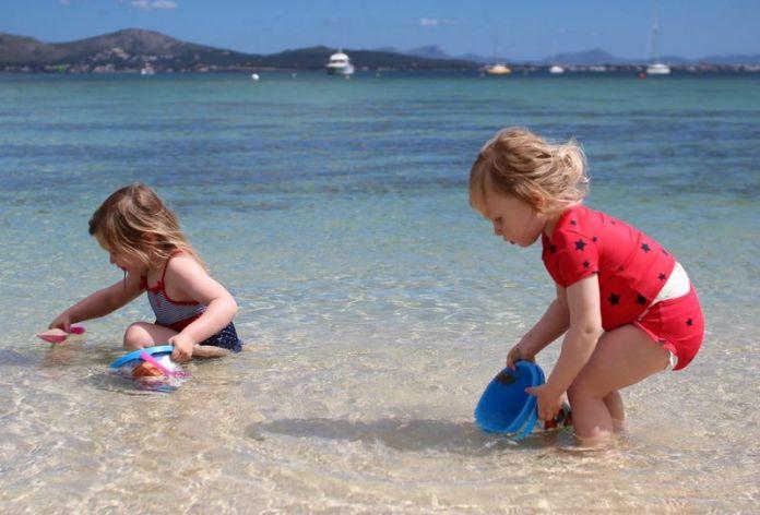 giochi da spiaggia: bambine cercano conchiglie in acqua