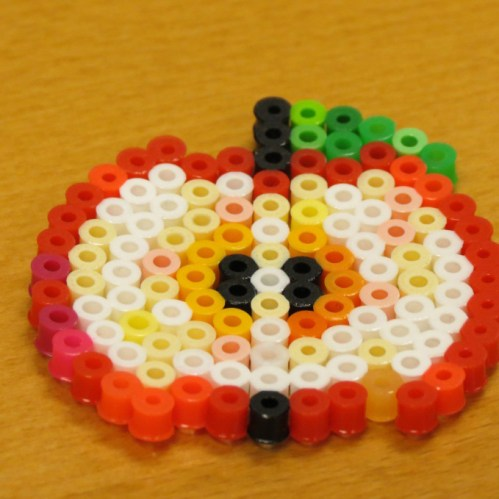 An apple created by fusing beads.