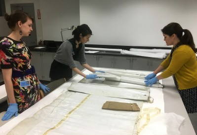 Bonnie, Laura, and Moya Dumville from West Lake Conservators carefully unroll objects to assess their condition before proceeding with treatment.