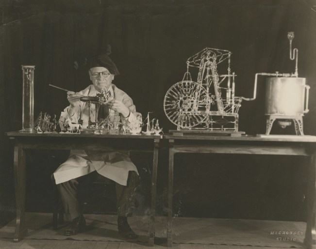 Black and white photograph of glassworker surrounded by his demonstration materials