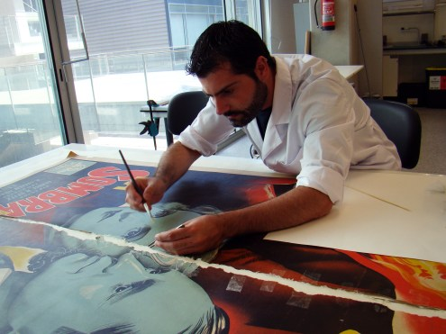Photograph of Pascual conserving a poster