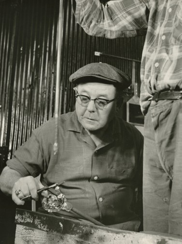 Photograph of a gaffer working on a piece of glass