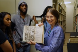 Librarian Beth Hylen gives students a tour of the special collections at the Rakow Research Library.