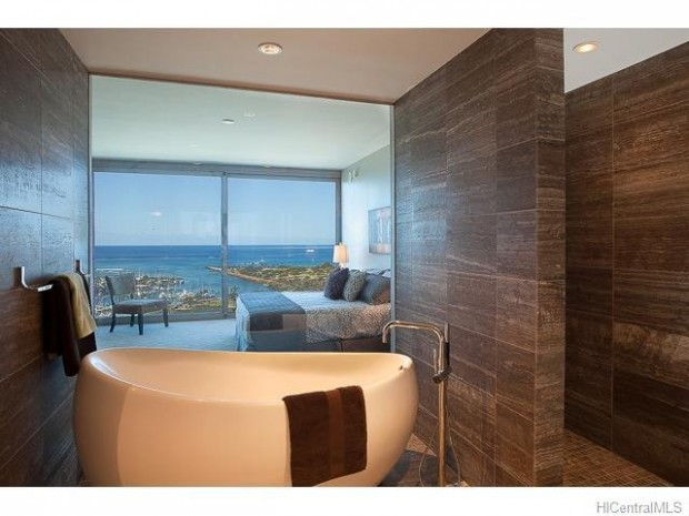 This Honolulu penthouse master bathroom features a free standing bathtub, as well as a glass wall which allows natural light to flow into the space. Located at 1555 Kapiolani Boulevard, Honolulu, HI this property is listed at $3.8 million by Iku S. Honda with Coldwell Banker Pacific Properties.