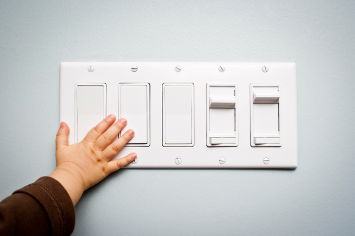 Baby hand touching a panel with five light switches