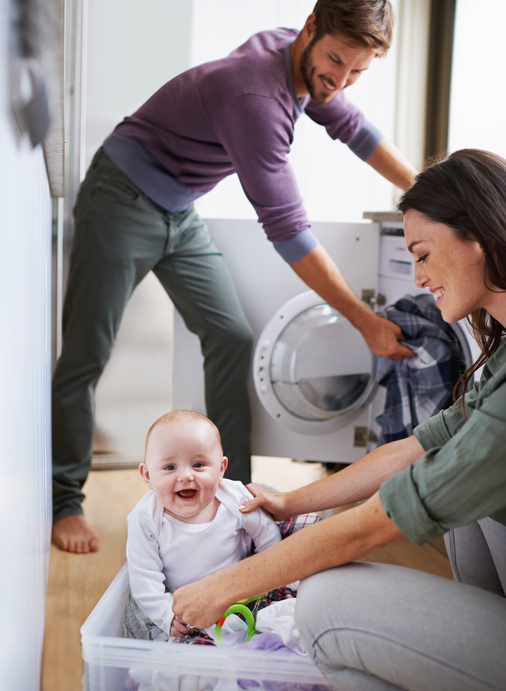 Shot of a young family having fun while doing laundry