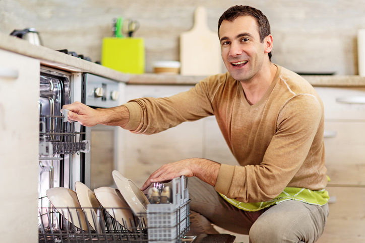 Smiling man using dishwasher.