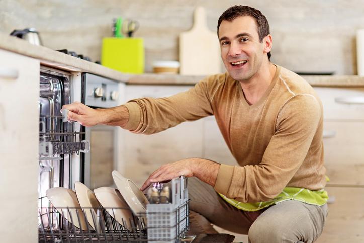 Smiling man using dishwasher.