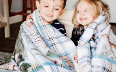 Two smiling kids wrapped in a photo blanket with blue plaid trim