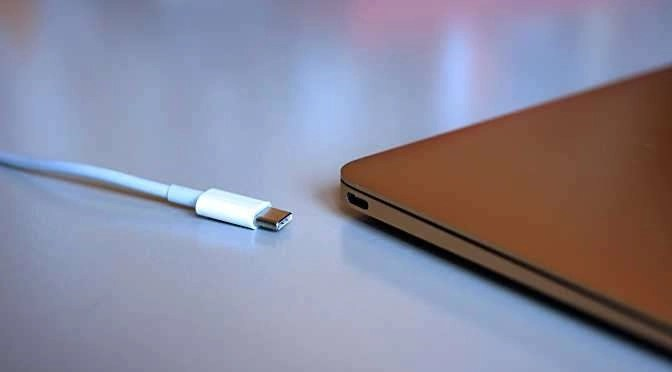 Een USB-C plug en connector op de laptop (bron afbeelding: https://commons.wikimedia.org/wiki/File:Apple_MacBook%27s_new_USB-C_(Type-C)_port_(17182398859).jpg)
