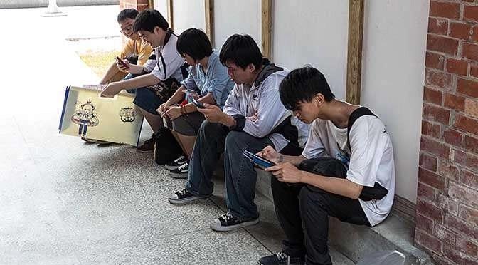 Digitale verslaving is in opkomst (bron afbeelding: https://commons.wikimedia.org/wiki/File:Visitors_Watching_Smartphones_after_Event_20140705.jpg)