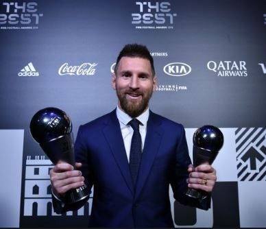 leo messi posing with the awards he received at FIFA the best gala.