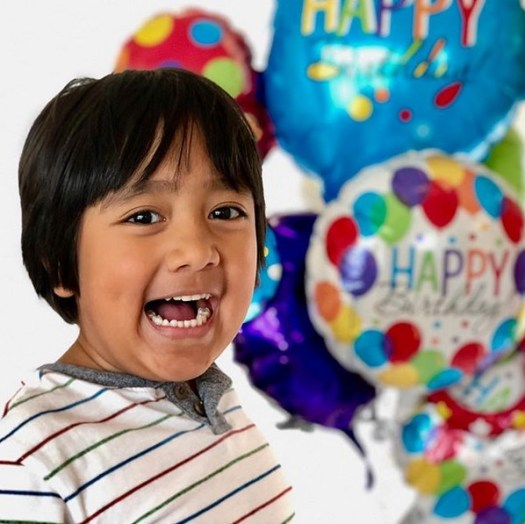 "Foto do Ryan ToysReview com alguns balões coloridos escrito ""Happy""."