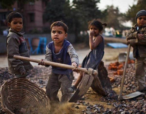 Indian children work nearby their parents at a construction project. Workers are being paid below the minimum wage in order to complete these projects whilst also being forced to live and work under substandard conditions. (Photo by Daniel Berehulak/Getty Images)
