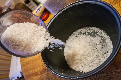 Pouring the rice into the rice cooker.