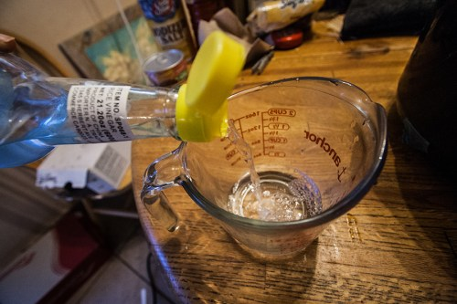 Pouring vinegar into a glass measuring cup, before adding sugar and salt.