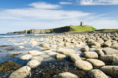Iconic Dunstanburgh castle ruin built in the 14th century viewed from the northern rocky shoreline