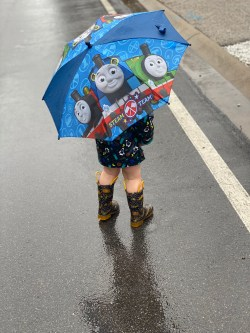 Toddler playing in rain with umbrella