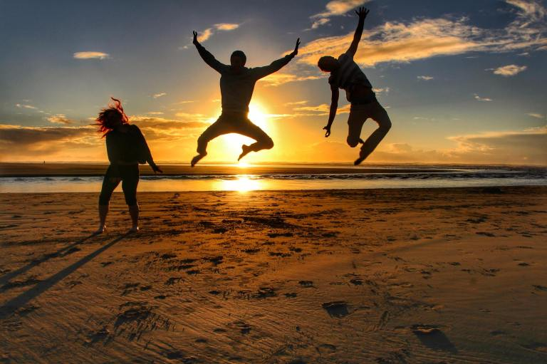 Couchsurfers jumping for joy after reaching the Pacific Ocean.