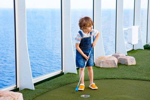 Little kid boy playing mini golf on a cruise liner.
