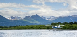 Float Plane in Alaska surrounded by snow capped mountains