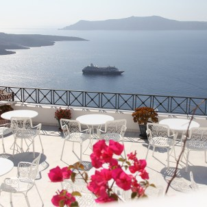 View from a Santorinihotel rooftop cafe overlooking a cruise ship sailing