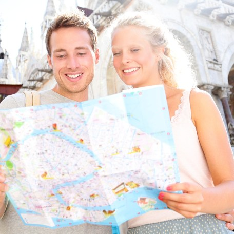 Romantic couple on tour in Venice using a local guide map