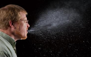 a man sneezing with pale droplets visible against the dark background