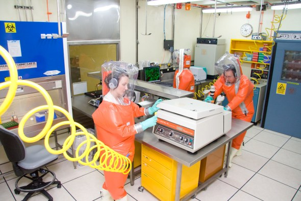Scientists in orange high containment suits inside lab