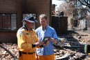 Two men holding a smart tablet standing in front of a burnt house
