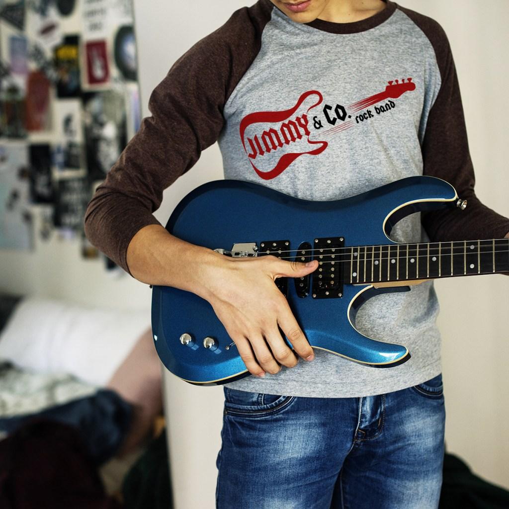 guy wearing raglan tee playing guitar